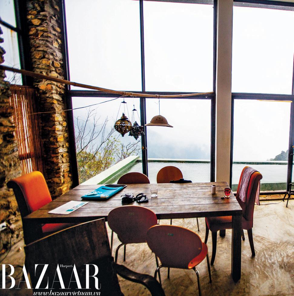 Chiếc bàn bằng gỗ nâu trầm thô mộc ở phòng khách kết hợp khéo léo với kiểu ghế hiện đại màu cam