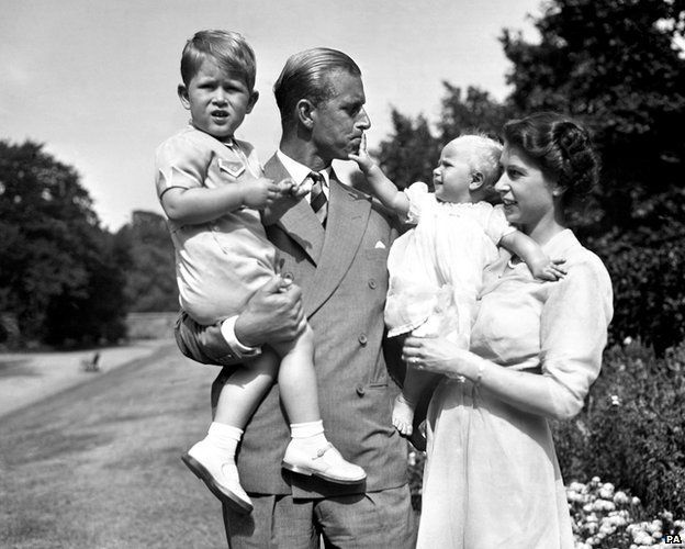 Princess Anne in the arms of Princess Elizabeth, with the Duke of Edinburgh, holding Prince Charles, in the grounds of Clarence House, their London residence, 1952
