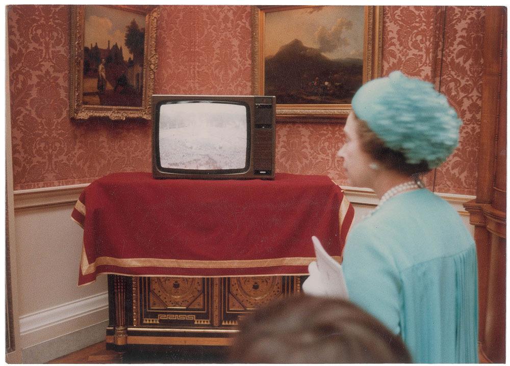 Bức ảnh cho thấy Nữ hoàng đang theo dõi hàng nghìn người tập trung trước lâu đài Buckingham qua ti vi.