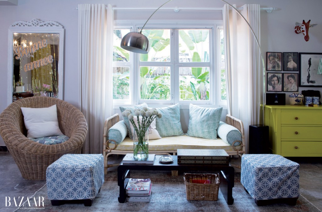 Một góc phòng khách được bài trí bộ bàn ghế mây và chiếc đèn đọc sách vòng cung