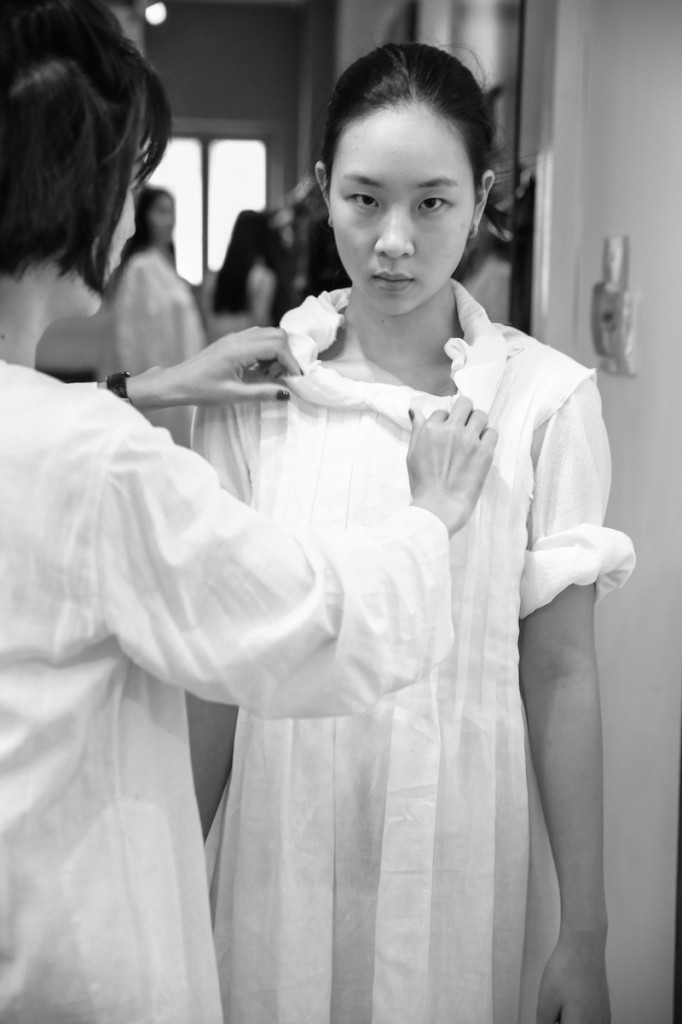 Nhà thiết kế Li Lam tỉ mỉ chỉnh sửa trang phục cho người mẫu