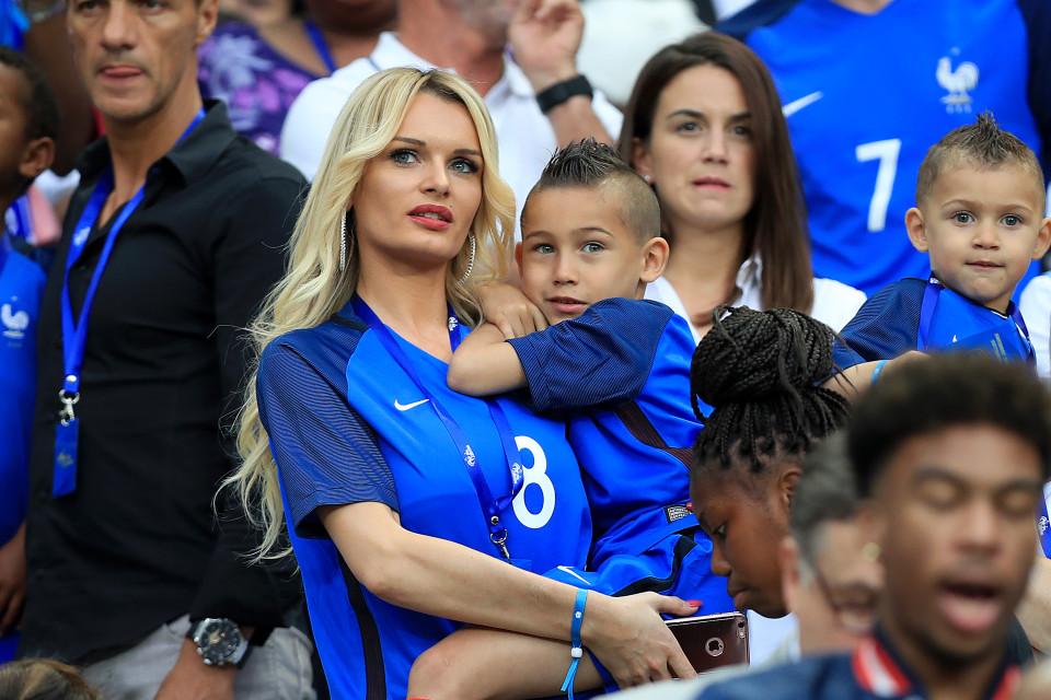 Ludivine Payet cùng con trai ngắm chồng mình là cầu thủ Dimitri của đội tuyển Pháp. Cô nổi bật trong màu son đỏ đúng phong cách Parisian chic