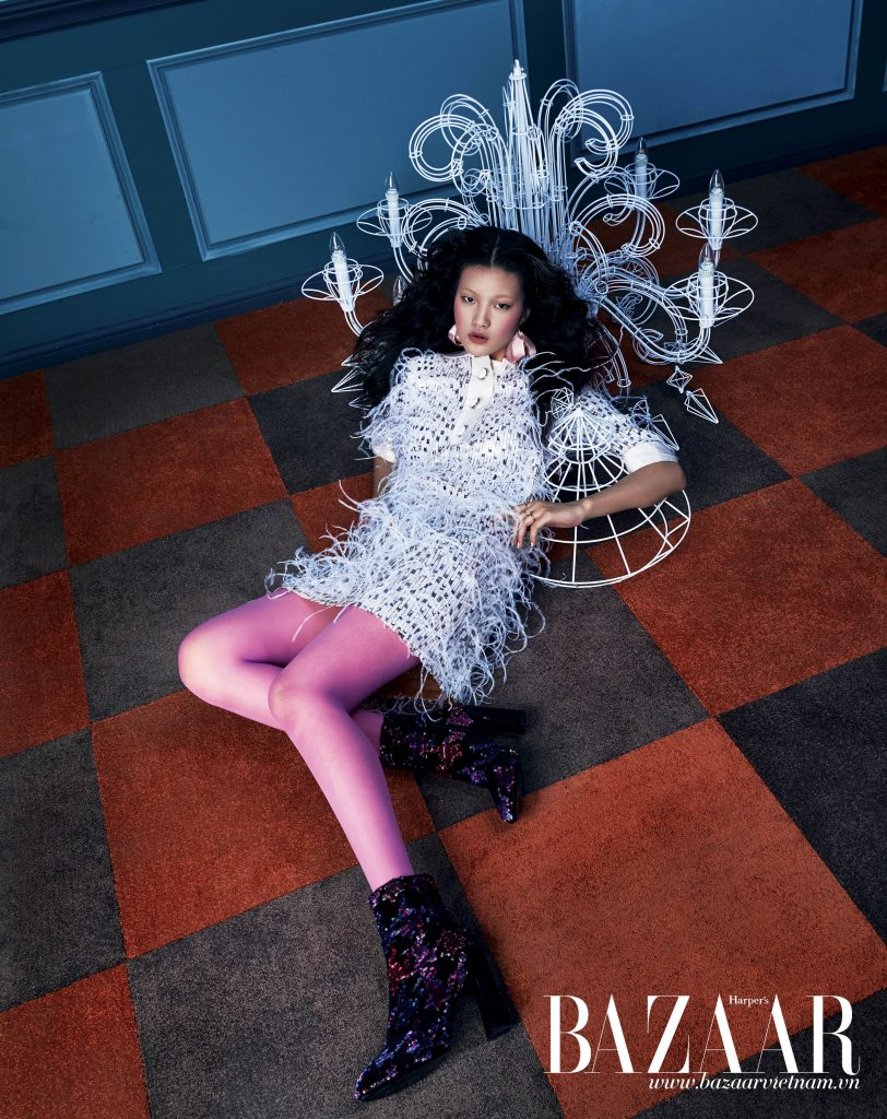 Đầm mini đính lông, Michael Kors Collection. Vớ hồng, Gucci. Hoa tai, H&M. Nhẫn, Louis Vuitton. Bốt ánh kim nhiều màu, Roger Vivier