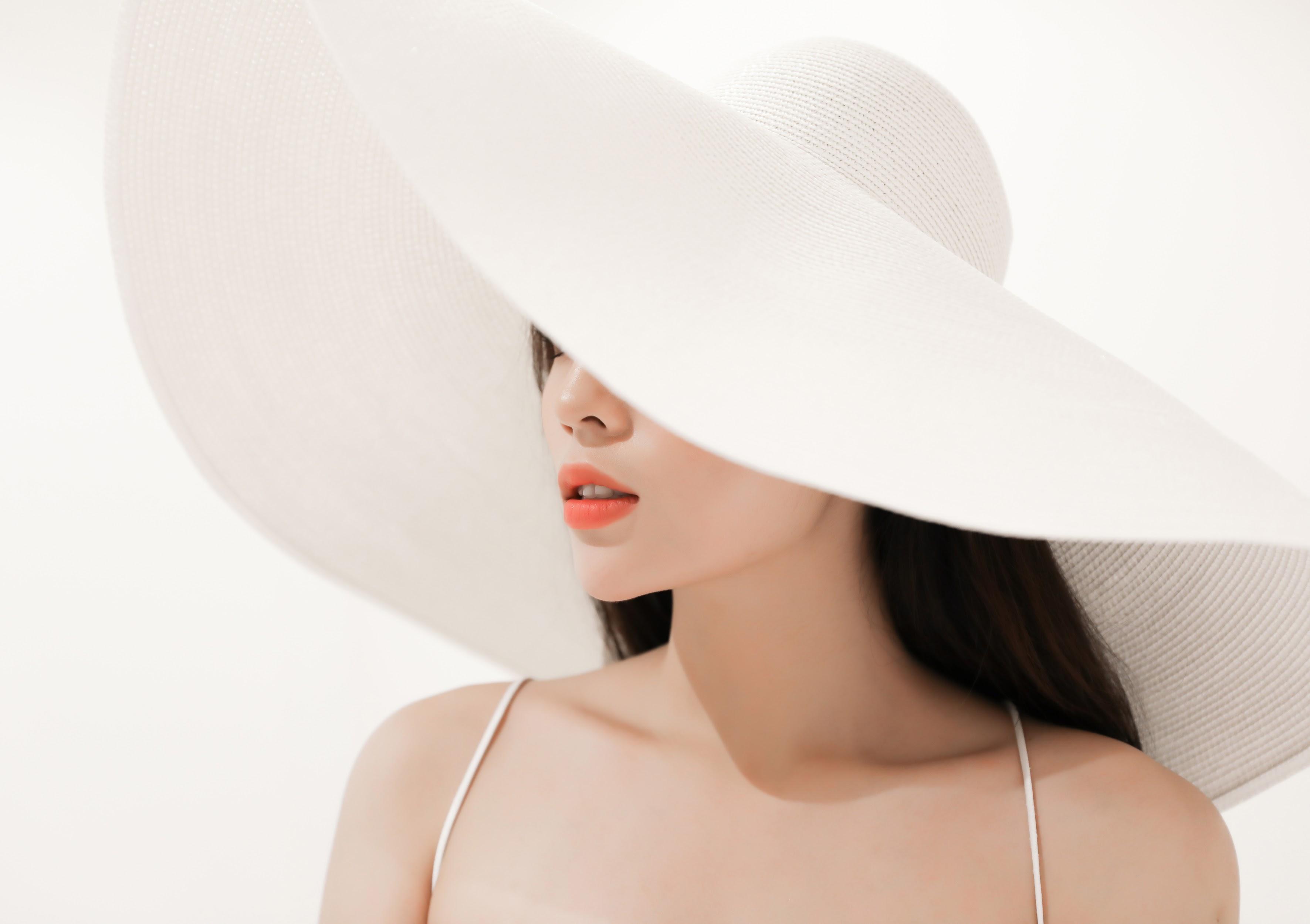 Chiếc mũ trắng tinh khôi làm điểm nhấn hoàn hảo cho toàn bộ trang phục.