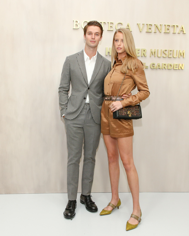 Người mẫu Abby Champion trong chiếc romper cotton màu camel, thắt lưng nhiều màu Ayers Patchwork, giày nhung d'Orsay và túi Karung Knot.