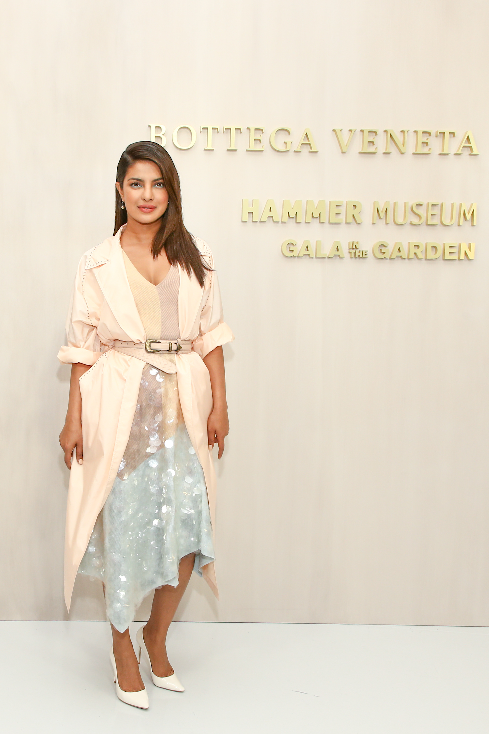 Diễn viên Ấn Độ Priyanka Chopra với chiếc áo khoác lụa màu đào, đầm đa sắc; cùng bộ đôi thắt lưng và hoa tai Peach Rose Intrecciato Nappa.