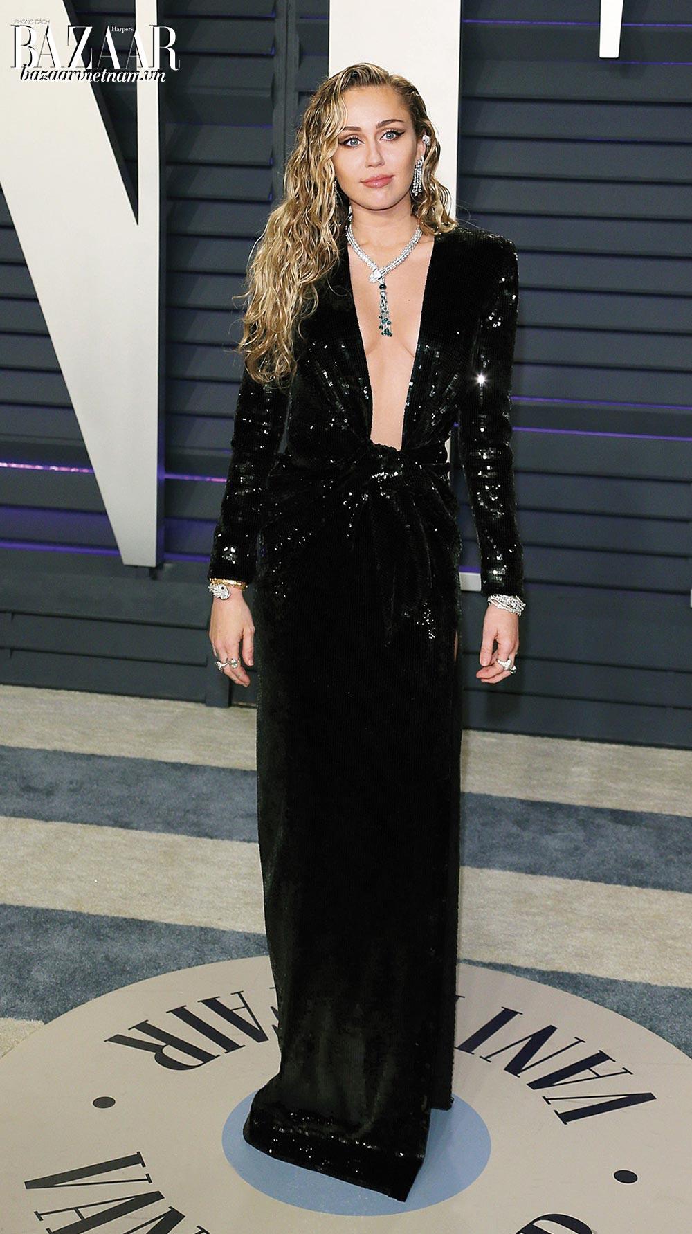"""Bộ đầm sequin xẻ bạo của Miley Cyrus là minh chứng cho cụm từ """"Dress-to-kill"""". Thiết kế màu đen không hề đơn điệu khi kết hợp với cổ áo xẻ sâu. Cô mặc thiết kế của Saint Laurent phối cùng trang sức Bvlgari."""