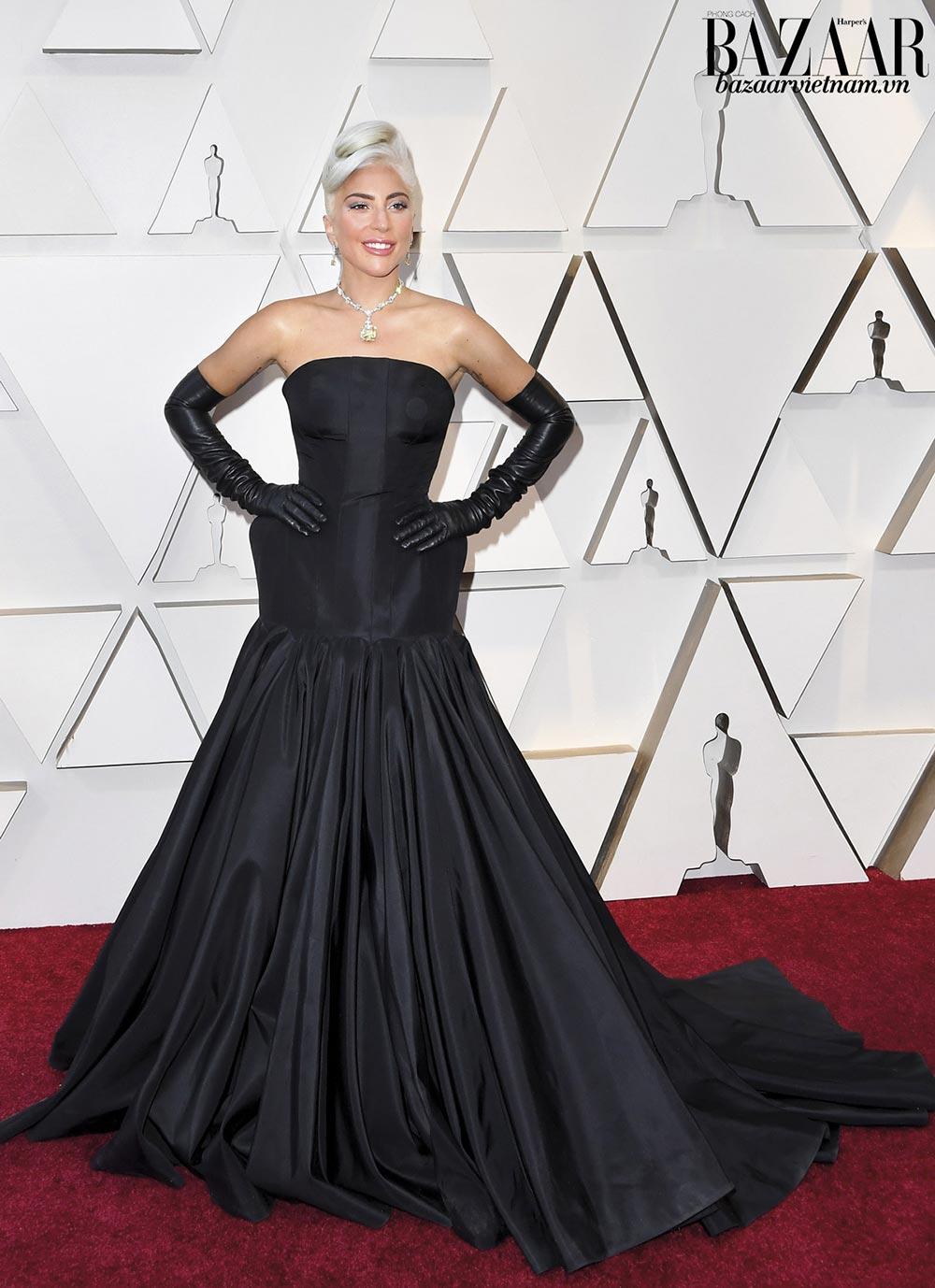 Lady Gaga tái hiện phong cách của biểu tượng Audrey Hepburn. Đầm đen của Alexander McQueen giúp nữ ca sỹ tôn mái tóc bạch kim và viên kim cương vàng của Tiffany & Co.