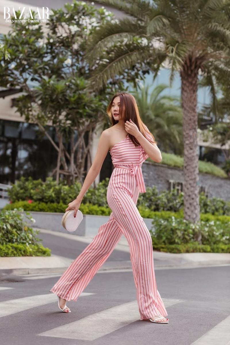 Bộ jumpsuit lệch vai cũng là trang phục yêu thích của siêu mẫu ngày nắng nóng. Họa tiết sọc dọc còn giúp các nàng ăn gian chiều cao và tôn dáng nữa đấy!