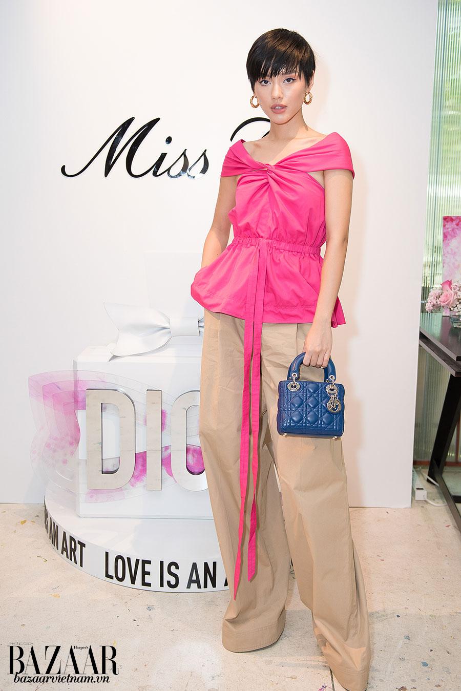 Khánh Linh The Face trông thật cá tính khi phối mái tóc tém ngắn, chiếc áo hồng rực cùng túi Lady Dior classic màu xanh biển theo phong cách color block.