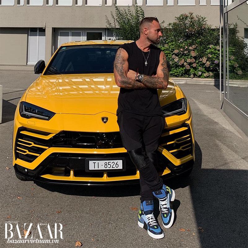 Đây không phải là lần đầu tiên Phillip Plein khoe giày và sưu tập siêu xe của mình. Trong hình, anh dựa trên chiếc Lamborghini vàng, nhằm khoe thiết kế giày xanh tương phản.