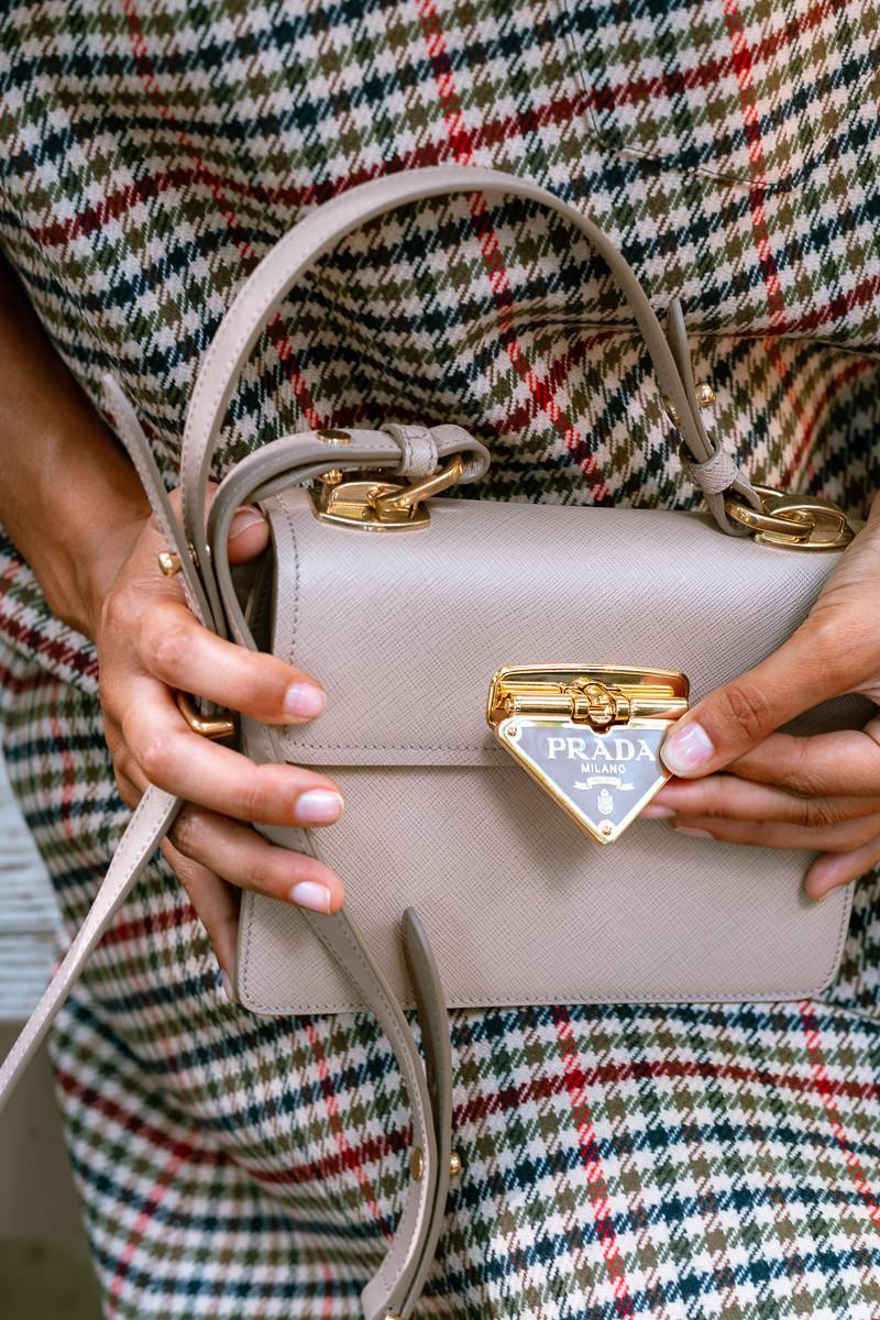 Prada biến logo tam giác thành khóa cài cho túi Symbole