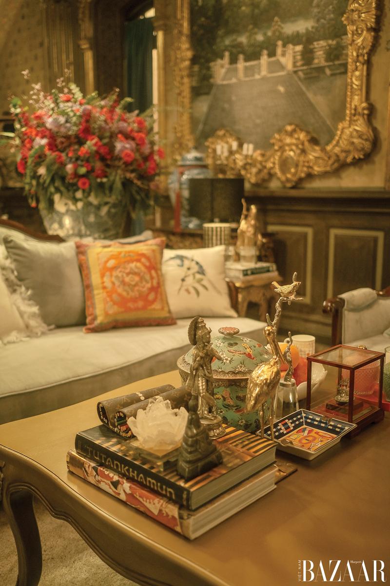 Phòng khách trang trí chỉn chu với những bức tượng đồng, đồ gốm sứ và bộ sách chuyên đề khảo cổ.