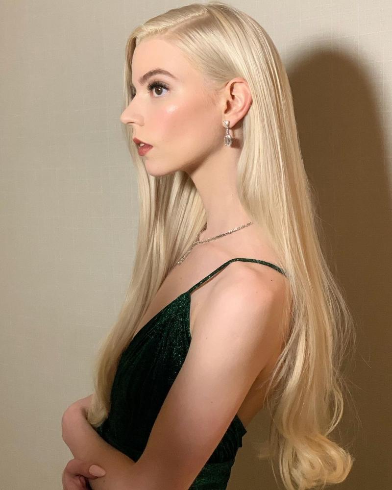 Trang điểm nhẹ nhàng nhưng sang trọng. Mái tóc vàng óng để xõa tự nhiên tôn lên vẻ đẹp quyến rũ của mỹ nhân The Queen's Gambit.