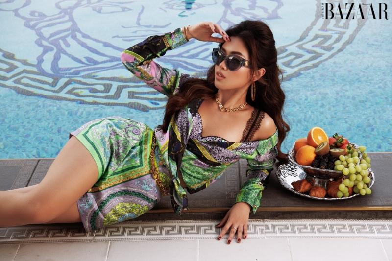 Tiên Nguyễn diện trang phục Versace bên hồ bơi với logo đầu rắn nổi bật của nhà mốt Ý.