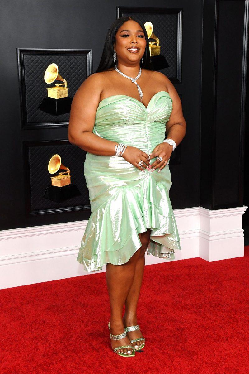 Rapper Lizzo chọn váy cúp ngực ôm sát màu xanh bạc hà đến từ nhà mốt Balmain. Cô phối cùng trang sức lấp lánh của Bulgari và cao gót dạ hội óng ánh từ Stuart Weitzman.