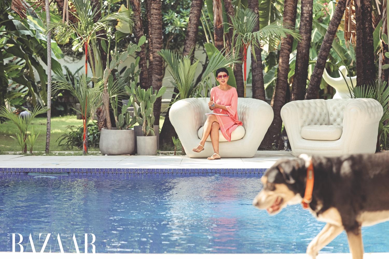 Marielle Genet Rakotomalala ngồi trên ghế sofa trắng để thư giãn, được bố trí quanh hồ bơi. Chú chó Ravitoto nghịch ngợm giúp ngôi nhà thêm sức sống.